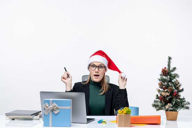New year mood with curious blonde woman with a santa claus hat sitting at a table with a christmas tree and a gift on it on white background