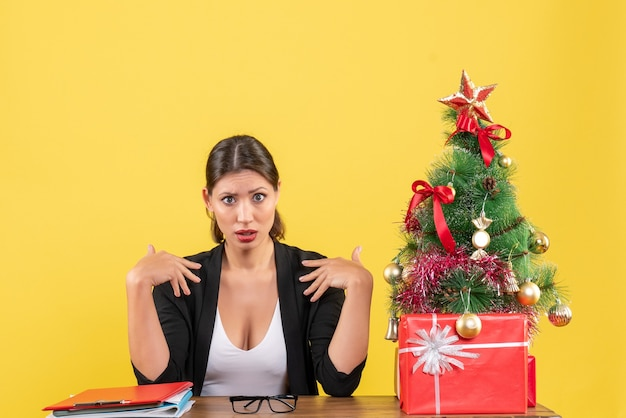 사무실에서 장식 된 크리스마스 트리와 소송에서 호기심 젊은 여자와 새해 분위기