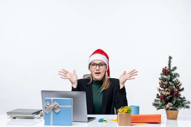 Umore del nuovo anno con una donna attraente determinata con un cappello di babbo natale seduto a un tavolo con un albero di natale e un regalo su di esso in ufficio