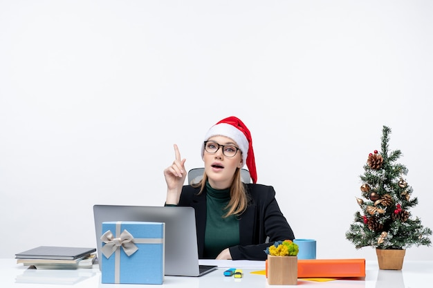 New year mood with determined woman with a santa claus hat sitting at a table with a christmas tree and a gift on it on white background