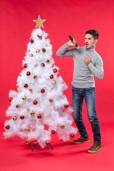 New year mood with emotional positive guy singing song standing near decorated christmas tree on red