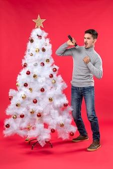 Umore del nuovo anno con il ragazzo positivo emotivo che canta la canzone che sta vicino all'albero di natale decorato sul rosso