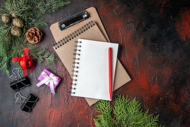 Atmosfera del nuovo anno con accessori per la decorazione di rami di abete e regalo accanto al taccuino con penna su sfondo scuro sopra vista