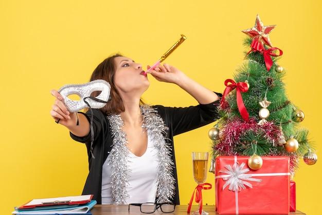 Новогоднее настроение с забавной очаровательной дамой в костюме, держащей маску в офисе
