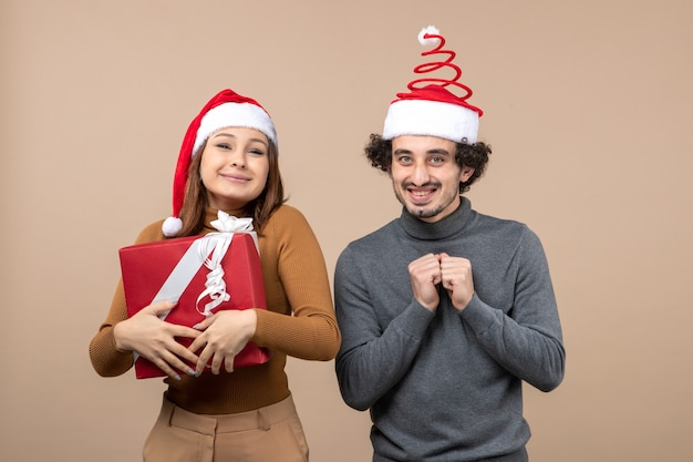 Umore del nuovo anno con le coppie adorabili divertenti che portano i cappelli rossi del babbo natale sulla foto grigia