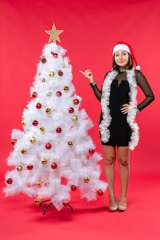 New year mood with happy beautiful girl in a black dress with santa claus hat pointing decorated christmas tree