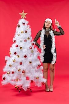 Новогоднее настроение со счастливой красивой девушкой в черном платье с шляпой санта-клауса, указывающей на что-то выше