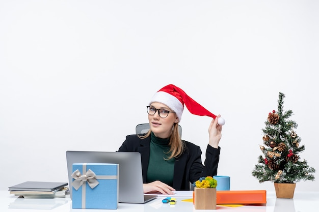 New year mood with positive blonde woman with a santa claus hat sitting at a table with a christmas tree and a gift on it on white background