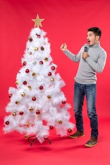 Новогоднее настроение с позитивным парнем в джинсах, стоящим возле украшенной елки