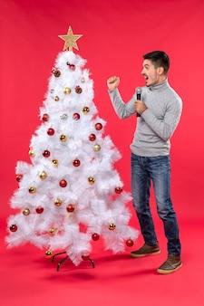 L'umore del nuovo anno con il ragazzo positivo si è vestito in jeans che stanno vicino all'albero di natale decorato che chiama qualcuno sul rosso