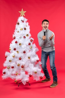 New year mood with positive guy singing song standing near decorated christmas tree on red footage