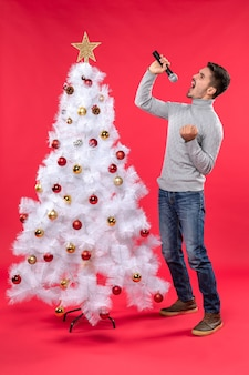 New year mood with positive guy singing song standing near decorated christmas tree on red stock image