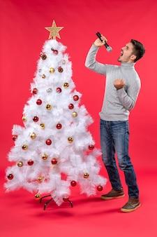 Umore del nuovo anno con il ragazzo positivo che canta la canzone che sta vicino all'albero di natale decorato sull'immagine di riserva rossa