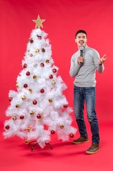 Umore del nuovo anno con il ragazzo positivo che canta la canzone che sta vicino all'albero di natale decorato sul rosso