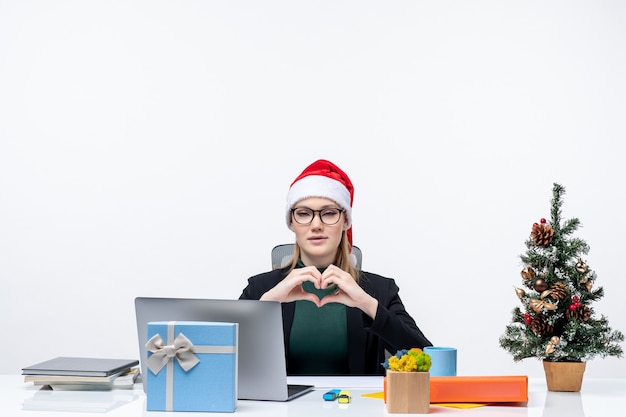 New year mood with romantic attractive woman with a santa claus hat sitting at a table with a christmas tree and a gift on it on white background