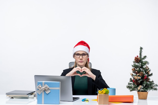 Umore di nuovo anno con donna romantica con un cappello di babbo natale seduto a un tavolo con un albero di natale e un regalo su di esso su sfondo bianco