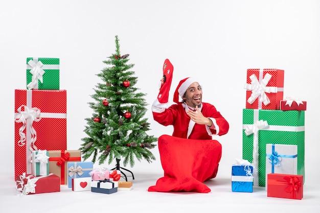 Новогоднее настроение с санта-клаусом, сидящим на земле и в рождественском носке возле подарков и украшенной елкой на белом фоне stock photo