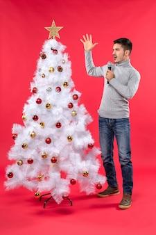 L'umore del nuovo anno con il ragazzo positivo scioccato si è vestito in jeans che stanno vicino all'albero di natale decorato