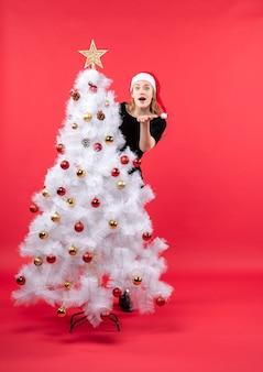 Umore di nuovo anno con giovane donna scioccata in abito nero e cappello di babbo natale in piedi dietro l'albero di natale bianco
