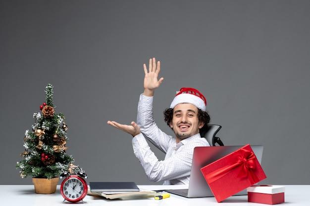 Новогоднее настроение с улыбающимся позитивным молодым бизнесменом в шляпе санта-клауса, сидящим в офисе и работающим в одиночку над проектом на темном фоне