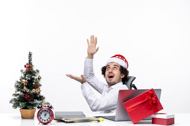 Umore del nuovo anno con il giovane uomo d'affari positivo sorridente con il cappello del babbo natale che si siede nell'ufficio e che lavora da solo sul progetto su fondo bianco