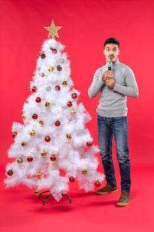 Новогоднее настроение с удивленным позитивным парнем в джинсах, стоящим возле украшенной елки на красном
