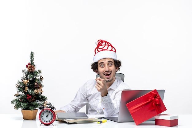 Umore del nuovo anno con il giovane uomo d'affari eccitato sorridente sorpreso con il cappello di babbo natale che chiede qualcosa nell'ufficio su fondo bianco