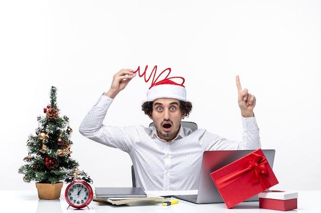 Новогоднее настроение с удивленным молодым бизнесменом, касающимся его забавной шляпы санта-клауса, указывающей выше в офисе на белом фоне