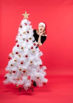 Umore di nuovo anno con giovane donna sorpresa in vestito nero e cappello di babbo natale in piedi dietro l'albero di natale bianco