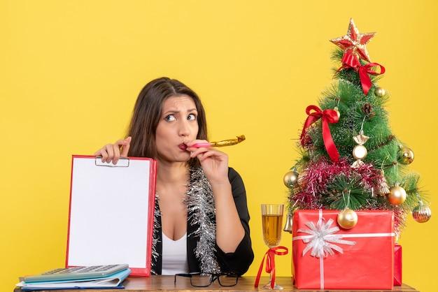 黄色の孤立したオフィスでドキュメントを保持しているスーツの思いやりのある魅力的な女性と新年の気分