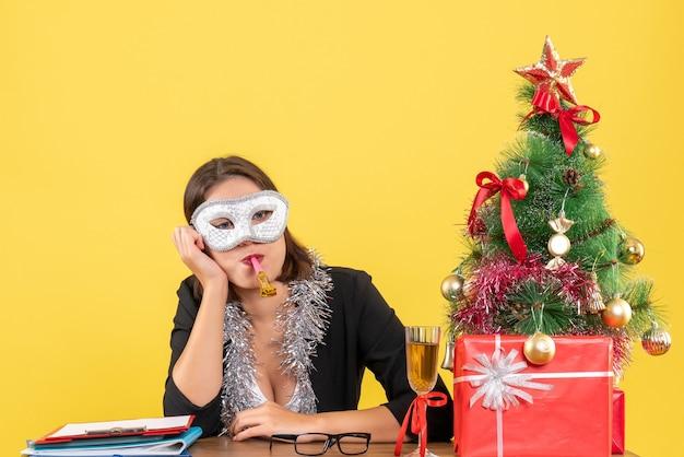 黄色の孤立したオフィスで深い考えでマスクを身に着けているスーツの思いやりのある魅力的な女性と新年の気分