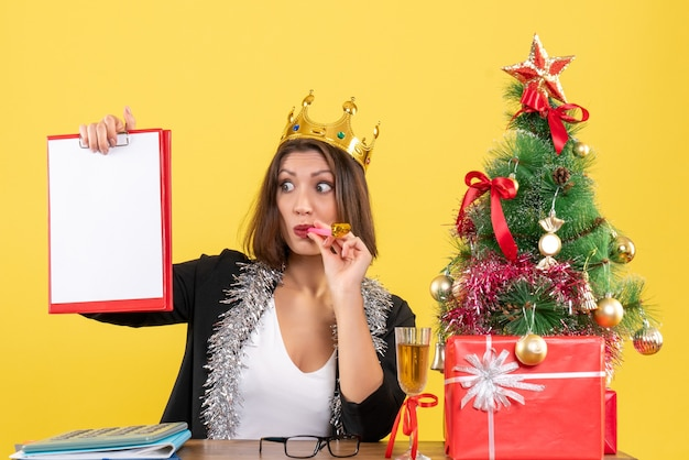 黄色の孤立したオフィスで文書を保持している王冠とスーツの思いやりのある魅力的な女性と新年の気分