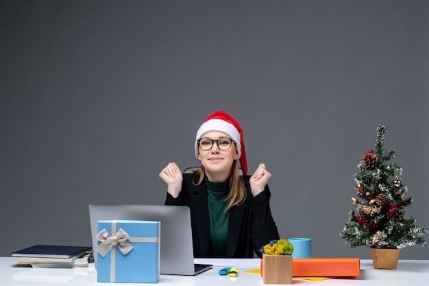 Новогоднее настроение с молодой привлекательной женщиной в шляпе санта-клауса, сидящей за столом с елкой и подарком на ней в офисе