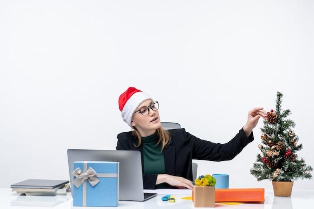 クリスマスツリーと白い背景の上の贈り物とテーブルに座っているサンタクロースの帽子を持つ若い魅力的な女性と新年の気分