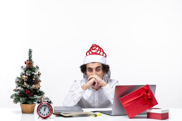 白い背景の上のオフィスですべてに疲れを感じている面白いサンタクロースの帽子を持つ若いビジネスマンと新年の気分