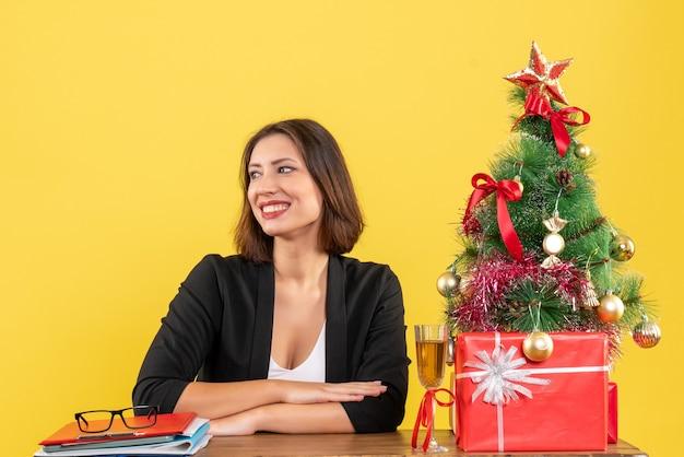 黄色で何かを見て、オフィスのテーブルに座っている若い幸せな感情的なビジネスの女性と新年の気分