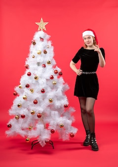New year mood with young woman in black dress and santa claus hat standing near white christmas tree