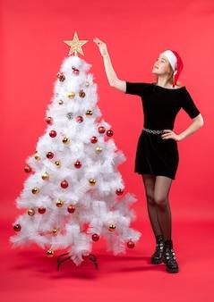 Umore del nuovo anno con la giovane donna in vestito nero e cappello di babbo natale in piedi vicino all'albero di natale bianco