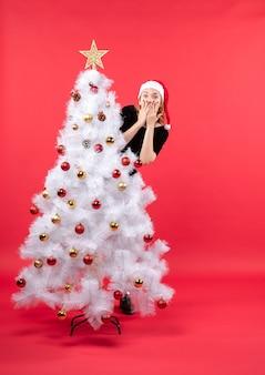 Umore del nuovo anno con la giovane donna in vestito nero e cappello di babbo natale in piedi dietro l'albero di natale bianco