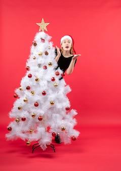 白いクリスマスツリーの後ろに立っている黒いドレスとサンタクロースの帽子の若い女性と新年の気分