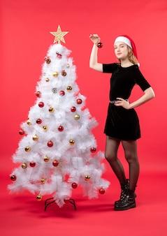 白いクリスマスツリーの近くに立っている黒いドレスとサンタクロースの帽子の若い女性と新年の気分