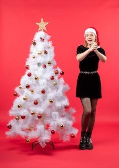 Новогоднее настроение с молодой женщиной в черном платье и шляпе санта-клауса, стоящей возле белой елки