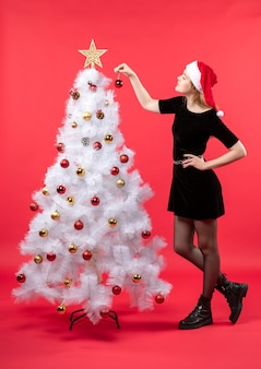 白いクリスマスの近くに立っている黒いドレスとサンタクロースの帽子の若い女性と新年の気分