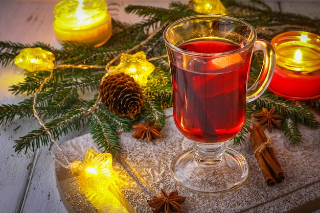 New year mulled wine in a glass on the background of twigs, candles and garlands.