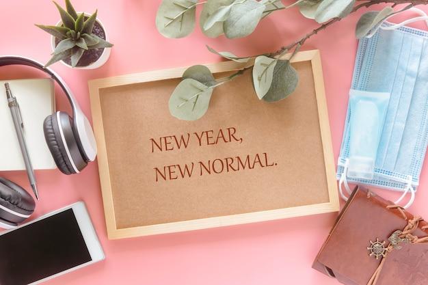 편지지, 스마트 폰, 마스크 및 손 소독제가있는 나무 편지지에 새해 새 정상이 평평하게 누워 있습니다. 새해에 새로운 정상적인 라이프 스타일을 제시하는 개념.