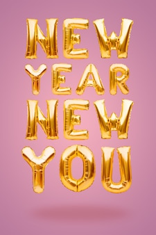 New year new you phrase made of golden inflatable balloons on pink background, new goal concept.