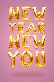 ピンクの背景に金色の膨脹可能な風船で作られた新年の新しいあなたのフレーズ、新しい目標の概念。
