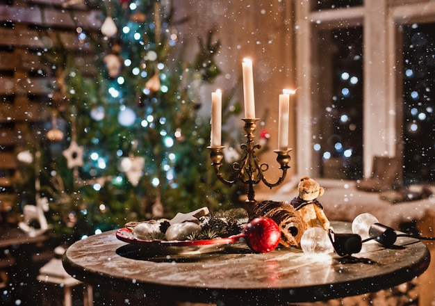 New year night table decoration with candles and antique decorations on the background of lights and christmas tree