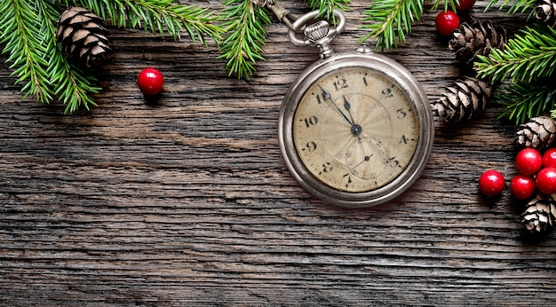 New year old pocket fob watch eve to midnight with fir branches, cones and decorations on rustic aged wooden table. copy space