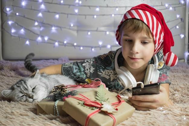 新年のオンライン挨拶。少年は猫と贈り物を持ってベッドに横たわっています。